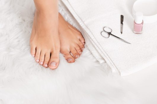 Beautiful female legs with pedicure tools, empty space